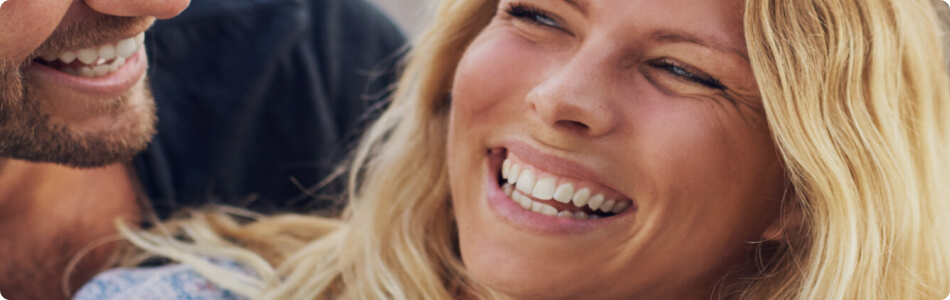 a young blonde woman smiling at her husband