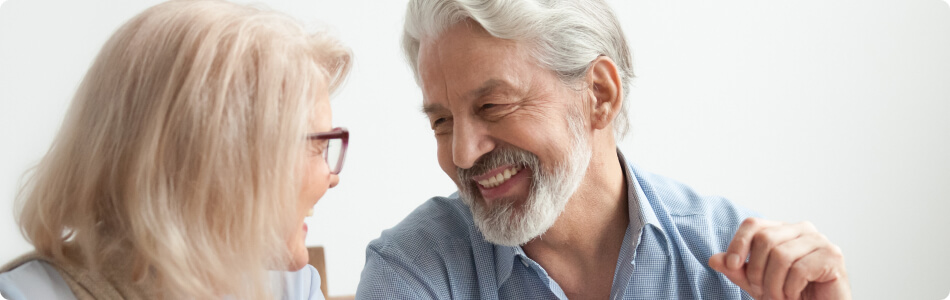 an older man and woman smiling at each other