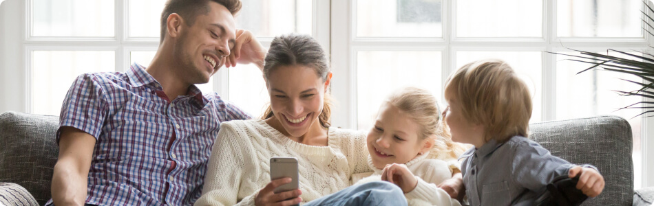 A dad, mom, little girl, and little boy sitting on the couch smiling and looking at a phone