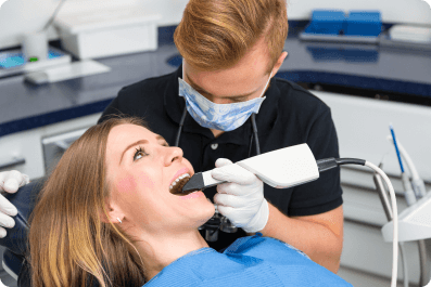 woman laying in a dentist chair while the dentist uses a laser in her mouth