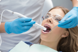 woman in a dental chair with her mouth open with dental tools inside